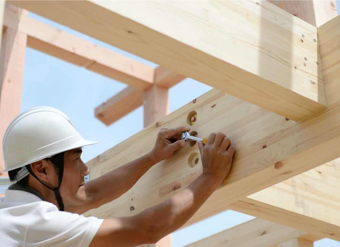 大工が木材に釘を打っている画像
